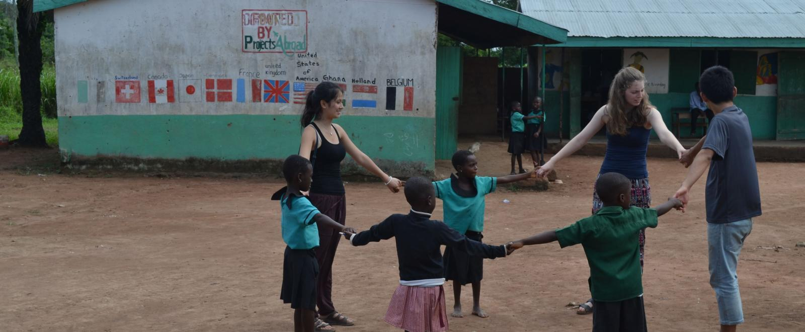 Group of teenage volunteers in Ghana play a game outdoors with children at a rural school.